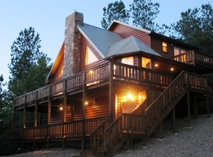 The Mountain Vista Luxury Cabin in Broken Bow exudes a serene glow as night falls.
