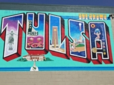 "The artist behind the iconic ""Greetings from Austin"" postcard mural repurposed this same theme on the walls of a Tulsa building, bringing life to this Tulsa Postcard Mural."