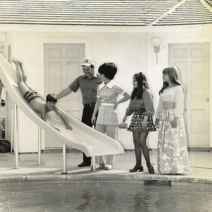 Conway Twitty and his wife Mickey watch their son, Jimmy, slide into the pool at the family's home in Moore, Oklahoma.