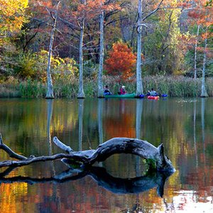 Fishermen chat in their canoes as fall beauty surrounds them at Beavers Bend State Park.