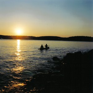 Paddlers enjoy a glorious sunset on Lake Tenkiller as they head their canoes towards shore.