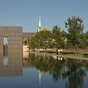 One of the Gates of Time, located on the grounds of the Oklahoma City National Memorial & Museum, reflects on the calm surface of the reflecting pond.