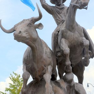 A cowboy wrangles a stray in this sculpture that greets visitors to the Historic Stockyards City near downtown Oklahoma City.  Stockyards City is the world's largest working cattle feeder and auction area and welcomes visitors to shop and dine as they co-mingle with cattlemen and ranch hands.