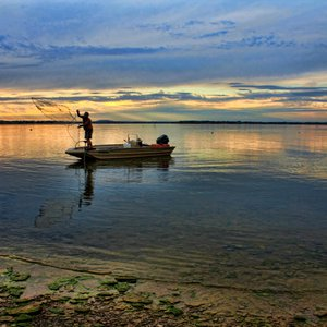 A fisherman casts for bait along the shores of Lake Eufaula.  A well-known tournament lake, Lake Eufaula draws anglers from across the United States to test their skills at catching largemouth bass, smallmouth bass, Kentucky bass, crappie, catfish, sandbass and other species.
