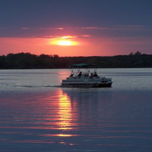 The sun sinks over the Fort Cobb Reservoir as a boat heads into Sunset Cove Marina within Fort Cobb State Park.