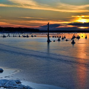 The brilliant colors of sunset cast a glow on the frozen surface of Lake Eufaula in this unusual winter landscape.