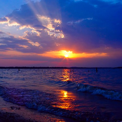 An outstanding Oklahoma sunset shines over the waves of Lake Eufaula.