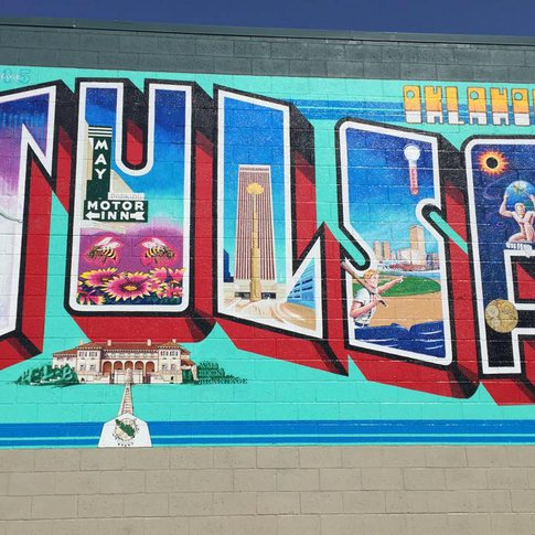 """The artist behind the iconic """"Greetings from Austin"""" postcard mural repurposed this same theme on the walls of a Tulsa building, bringing life to this Tulsa Postcard Mural."""