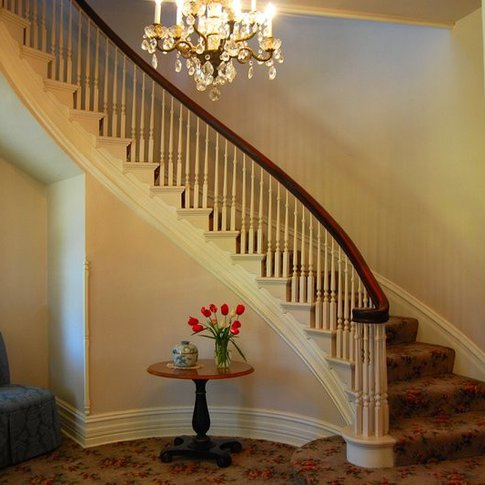 The exquisite staircase of the Pecan Valley Inn Bed & Breakfast curls upward around a crystal chandelier.