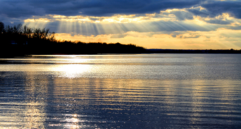 Rays of light radiate through the clouds creating a beautiful sunset over Lake Eufaula.