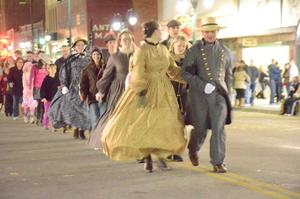 Dancers fill the streets during the Dickens on the Boulevard event, an annual holiday celebration.