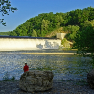 An angler enjoys fishing below the spillway at Spavinaw Area at Grand Lake State Park.